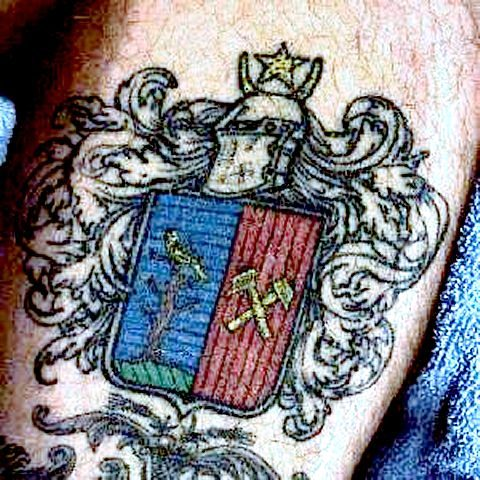 Photograph of the Mumma Coat of Arms tattooed on the leg of Craig Mumma It